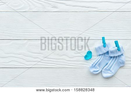 baby socks at wooden background top view