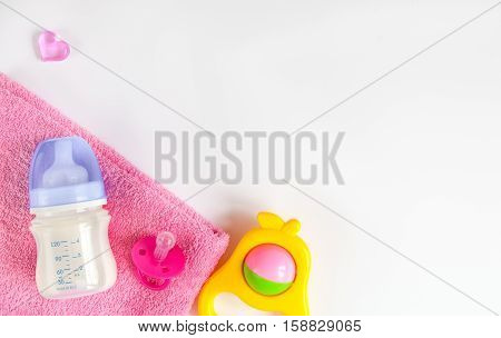 baby bottle with milk and towel on white background top view