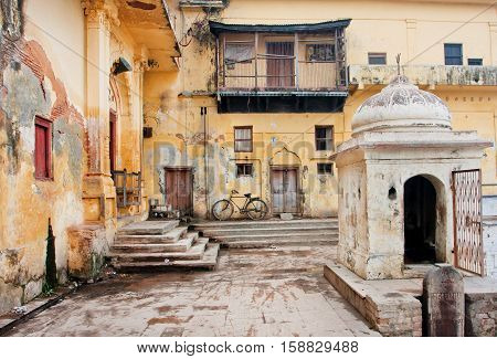 AYODHYA, INDIA - JAN 28, 2013: Old bycicle stands in the courtyard of poor historical indian house on January 28, 2013. Ayodhya had a population of 49593. 12 perc. of the population is under 6 years of age