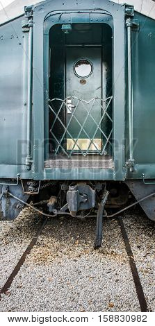 End of historic railroad pullman train car with door and round window