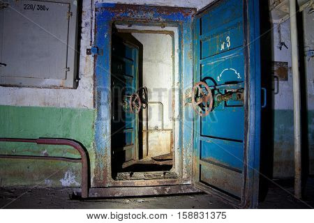 Blue rusty hermetical door of old abandoned Soviet bomb shelter