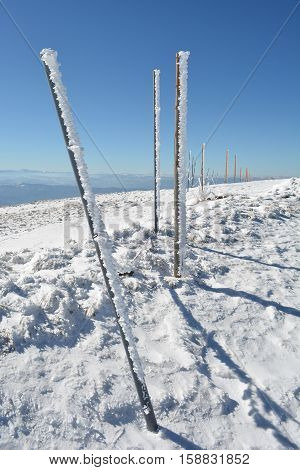 Iron and wooden pillars covered with icicles in long row on the top of the mountain necessary assistance to skiers in foggy winter days vertical orientation