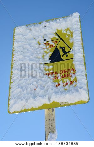 Sign danger on ski almost completely covered by snow and icicles