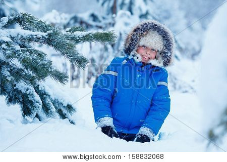 Cute little boy wearing warm clothes playing on winter forest on beautiful winter snowy day
