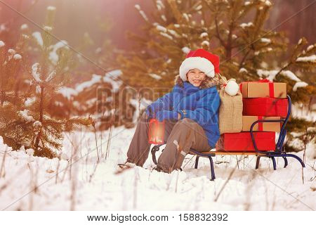 Cute little boy in Santa hat holding Christmas lantern and carries a wooden sled full of gift boxes in snowy forest. Xmas, snow and winter fun for family