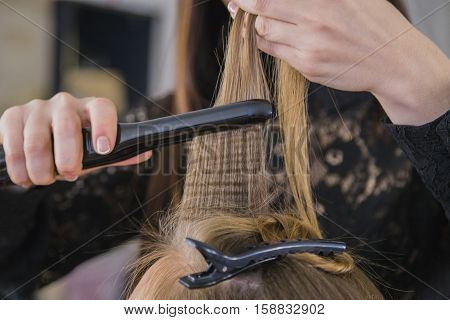 Closeup of hairdresser straightening the hair of a client