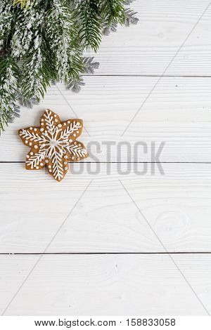Christmas gingerbread, spruce branches on wooden background top view.