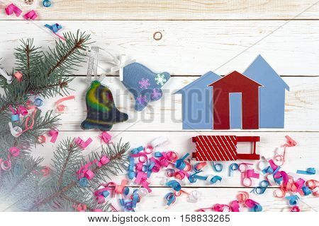 Christmas card . Fir branches Christmas toys on wooden background. House and key on wooden background