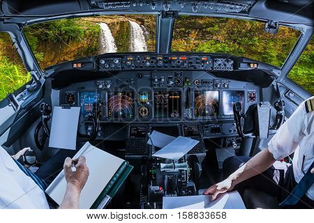 Airplane cockpit flying on ropical Manawaiopuna Falls also called Jurassic Park Falls, Kauai, Hawaii, United States, with pilots arms and blank white papers for copy space.