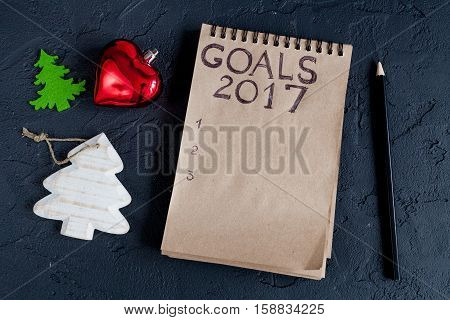 notebook and goals for new 2017 year on dark background top view