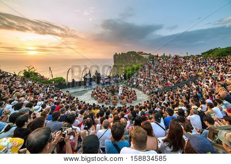 Bali, Indonesia - September 19: Tourists watch traditional Balinese Kecak Dance at Uluwatu Temple on Bali, Indonesia. Kecak (also known as Ramayana Monkey Chant) is very popular cultural show on Bali.