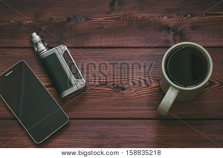e-cig mod or electronic cigarette for vaping and smart mobile phone, cup of tea or coffee on a wooden background. vape device and mobile gadget. copy space