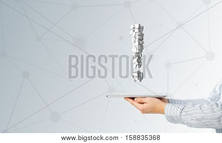 Hand of businessman showing tablet pc with exclamation mark on screen
