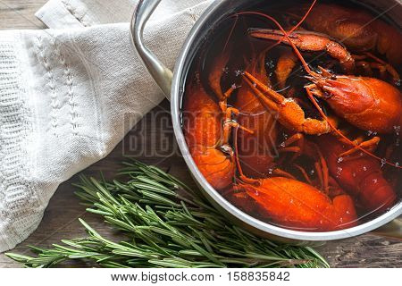 Pot with boiled crayfish on the wooden table