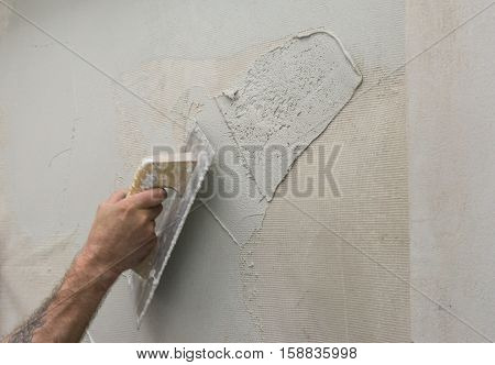 Hand holding a trowel, applying a microcement thick preparation layers on wall covering microtopping coating whit fiberglass mesh