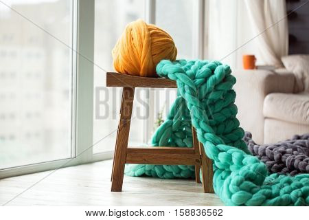 Orange wool ball with green knitted merino wool blanket on wooden chair orange cup on a sofa at the background