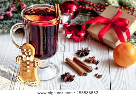 Christmas mulled wine with spices in cup on wooden background close up