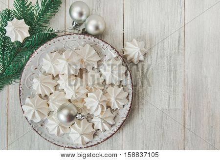 Sweet christmas background with airy meringues fir branchsilver ballsplate.Wooden table.Top view