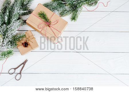 gifts boxes with fir branches on wooden background top view.
