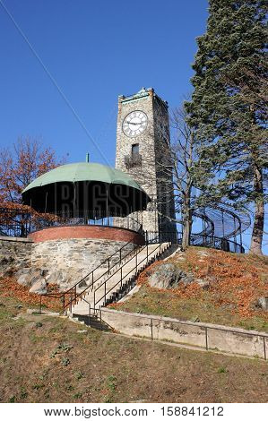 19th century stone clock tower constructed on a rocky outcropping.