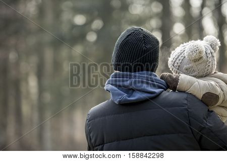 Parent holding a young child in warm woolly clothing on a winter day facing away towards a misty forest lateral copy space.