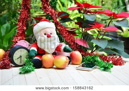 Santa claus doll, apples and smart phone on christmas day.