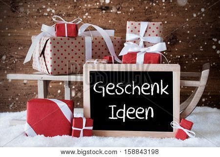 Chalkboard With German Text Geschenk Ideen Means Gift Ideas. Sled With Christmas And Winter Decoration And Snowflakes. Gifts And Presents On Snow With Wooden Background.