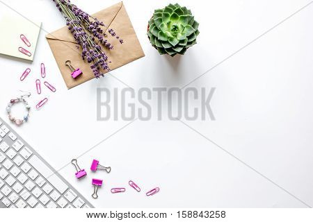 female white desktop with flowers, keyboard, paper envelopes top view no one