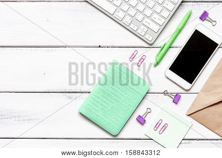 female wooden desktop with smartphone, keyboard, paper envelopes top view no one