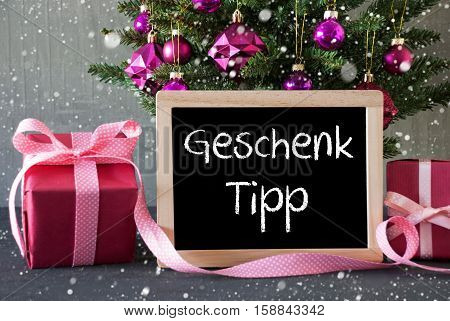 Chalkboard With German Text Geschenk Tipp Means Gift Tip. Christmas Tree With Rose Quartz Balls, Snowflakes. Gifts Or Presents In The Front Of Cement Background.
