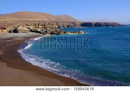View on the beach Playa de Ajuy with a single person enjoying the ocean on the Canary island Fuerteventura Spain.