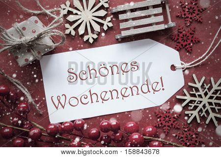 Nostalgic Christmas Decoration Like Gift Or Present, Sleigh. Card For Seasons Greetings With Red Paper Background. German Text Schoenes Wochenende Means Happy Weekend