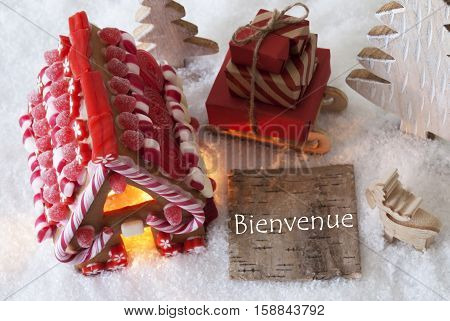 Label With French Text Bienvenue Means Welcome. Gingerbread House On Snow With Christmas Decoration Like Trees And Moose. Sleigh With Christmas Gifts Or Presents.