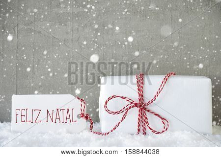 One Christmas Present On Snow. Cement Wall As Background With Snowflakes. Modern And Urban Style. Card For Birthday Or Seasons Greetings. Label With Portuguese Text Feliz Natal Means Merry Christmas