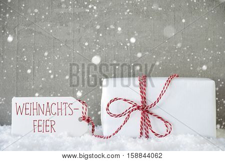 Label With German Text Weihnachtsfeier Means Christmas Party. One Christmas Present On Snow. Cement Wall As Background With Snowflakes. Modern And Urban Style.
