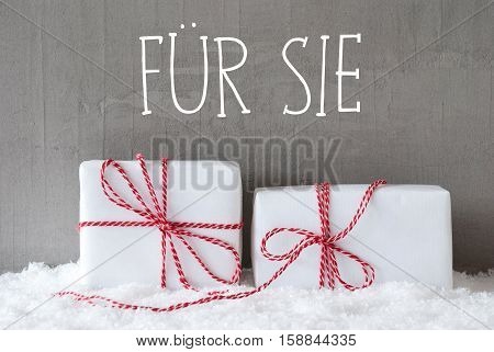 German Text Fuer Sie Means For Her. Two White Christmas Gifts Or Presents On Snow. Cement Wall As Background. Modern And Urban Style.