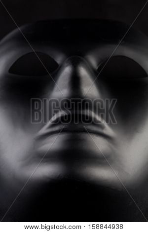 Anonymous Black Mask Protruding From Pitch Black Background - Hero Shot.