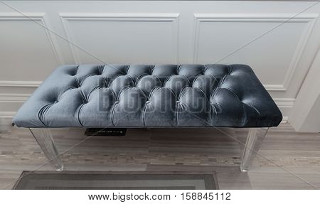 Soft cozy and comfortable ottoman leather bench in the house hallway on hardwood floor beside the wall