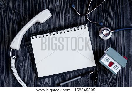 Entry to the doctor blank open notebook with stethoscope top view on dark wooden background