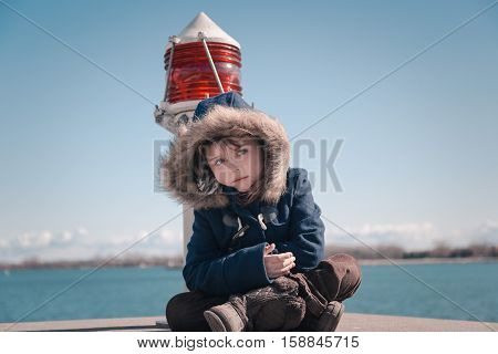 sad lonely little girl sitting  and looking aside near the harbor beacon light on sunny fresh, cold day