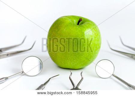 dental tools on with apple white background close up