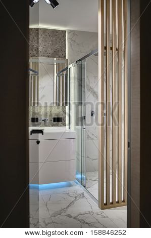 Door to the bathroom in the interior in a modern style. There is a wooden wall, white tiles with patterns and mosaic on the walls, white sink with mirror, shower with glass door, glowing lamps.