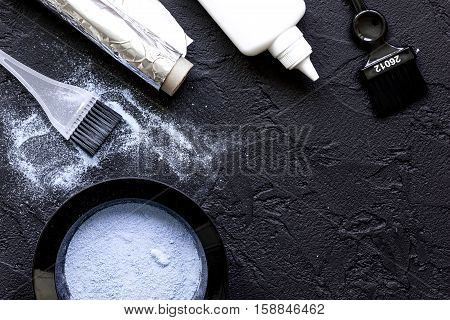 hair dye with brush on dark background top view.