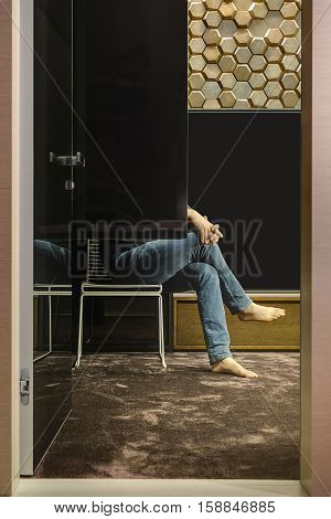 Interior in a modern style with a carpet on the floor and a wooden wall textured with hexagons. There is an open door of the glassy wardrobe, barefoot man sitting on a white chair, wooden rack.