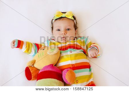 Face of cute surprised baby infant girl in colored pajamas with a bow on her head, making funny mouth expression. on a white blanket