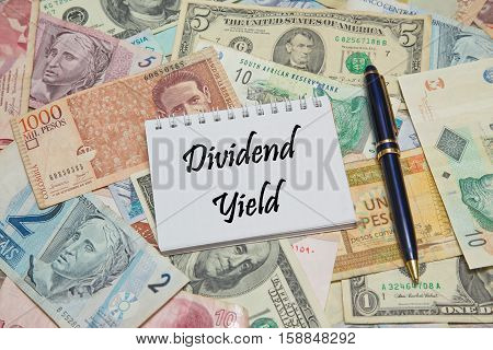 Notebook page with text DIVIDEND YIELD, background from different world Currencies