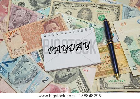 Notebook page with text PAYDAY, background from different world Currencie