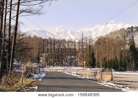 Village road in Iwatake, Hakuba, heading towards the snow covered mountain range backdrop. Covered walkways, offering protection in bad weather, appear on both sides of the road.