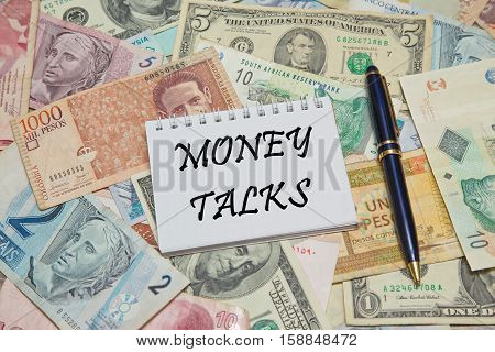 Notebook page with text MONEY TALKS, background from different world Currencies