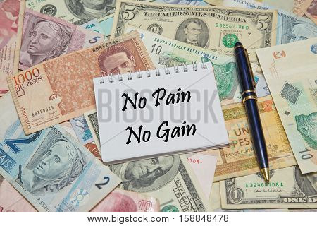 Notebook page with text NO PAIN NO GAIN, background from different world Currencies